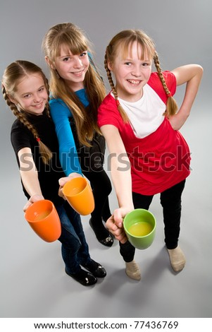 Three cute little girls with colorful mugs - stock photo