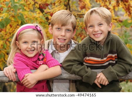 three cute siblings together outside with bright colored background - stock photo