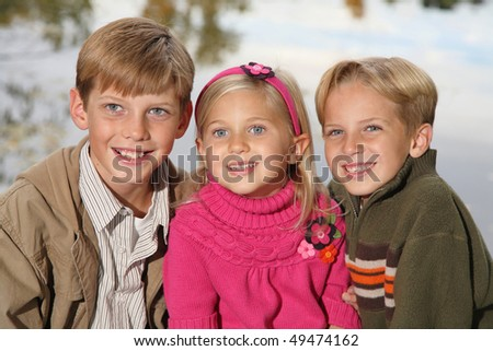 three cute siblings together outside with water background - stock photo