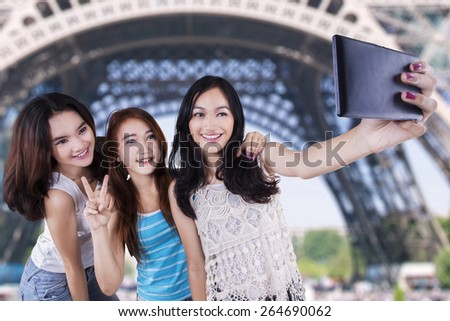 Three cute teenage girls using a mobile phone to take self picture at Eiffel Tower - stock photo