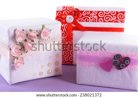 Three cute white present boxes on purple surface isolated on white - stock photo