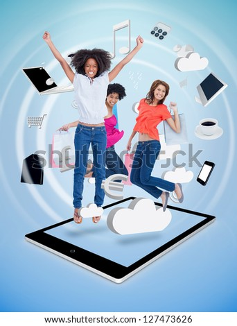 Three cute women jumping on a tablet pc against a digital blue background - stock photo