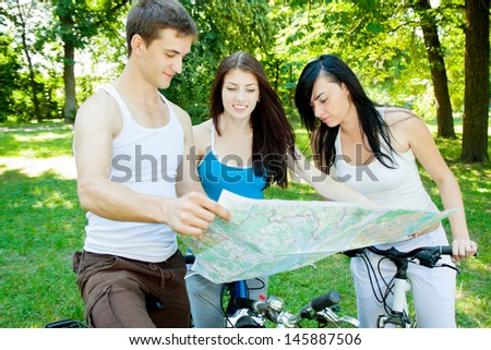 Three cyclists consider the map in the forest - stock photo