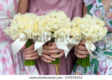 three daffodil wedding bouquets held by bridesmaids in vintage dresses - stock photo
