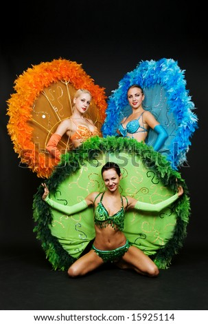 three dancers in stage costumes over dark background - stock photo