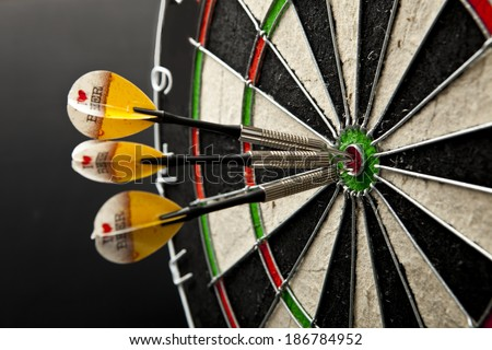 Three darts in bullseye of dartboard