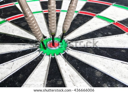 Three darts in the centre of a dartboard - stock photo
