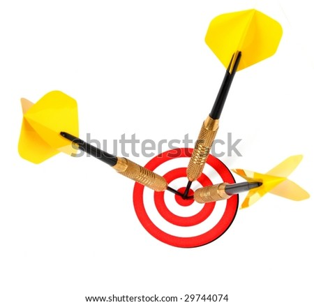 three darts pinned to the center of the same target - stock photo