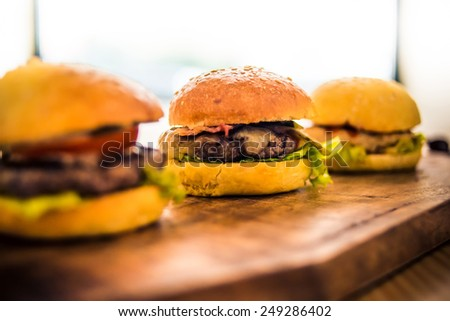 Three delicious hamburgers on wooden board - stock photo