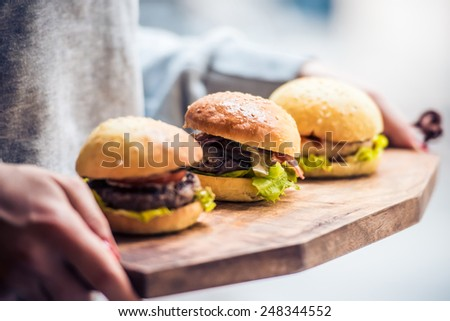 Three delicious hamburgers on wooden board. Toned image - stock photo