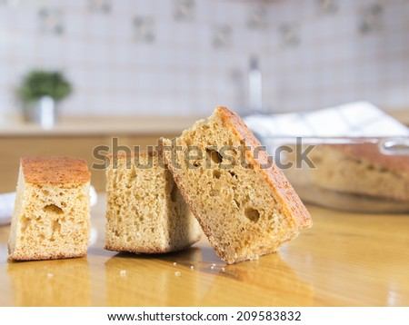 Three delicious pieces of cake in a wood table with the rest in a oven tray