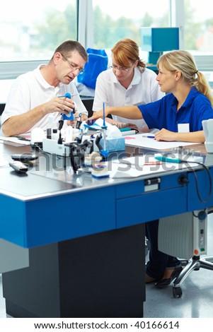 Three dental technicians working in a dental laboratory - stock photo