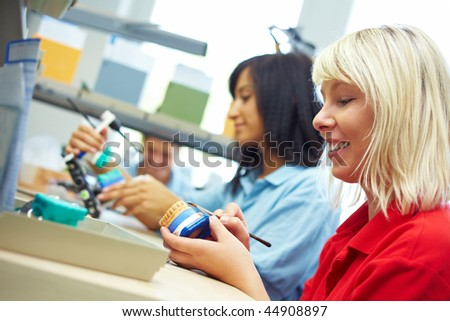 Three dental technicians working in a dental laboratory - stock photo