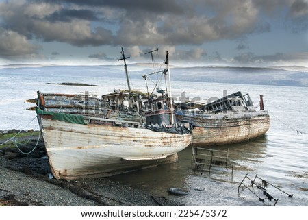 Three derelict fishing trawlers hauled up and rotting in a sea estuary - stock photo