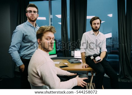 Three developers working on a project and communicating together at trendy start up office, discussing project on a computer screen. Chroma key.
