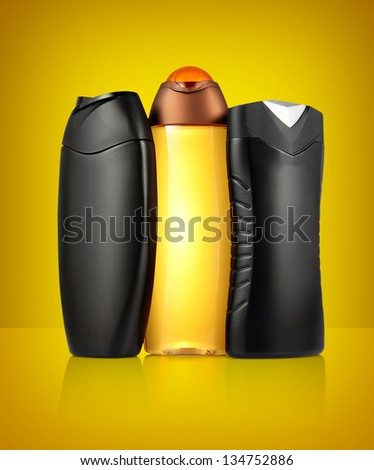 Three different black and orange tubes and bottles for hygiene, health and beauty on a orange background with reflection. - stock photo