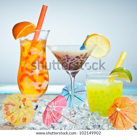 Three different boba tea cocktails with mango, orange, coffee and lime flavored. With paper umbrellas. - stock photo