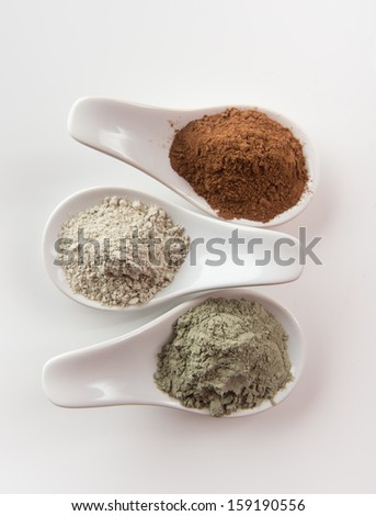 Three Different Clay Mud Powders, Red Mud, Bentonite and Green Clay in Ceramic Spoons
