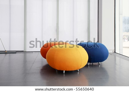 three different color rounded sofas isolated in morden house - stock photo