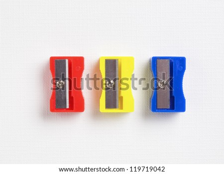 three different colors sharpener on white background - stock photo