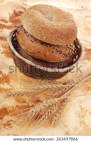 three different fresh bagels  over baking paper as background - stock photo