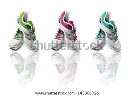 Three different pairs of colors Sport shoes with reflection isolated on white background  - stock photo