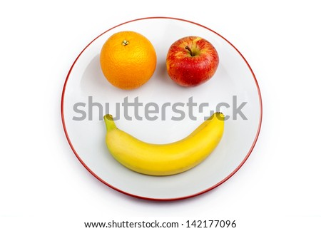 Three different pieces of fruit making up a smiling face on a plate over a white background. - stock photo