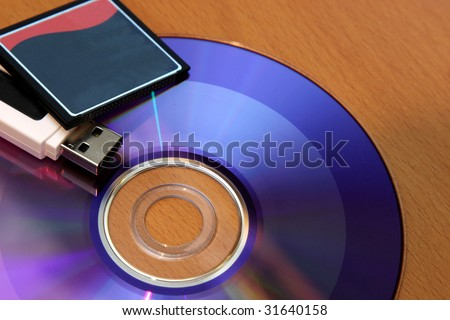 Three different pieces of media storage. (USB stick, compact flash and a DVD) - stock photo