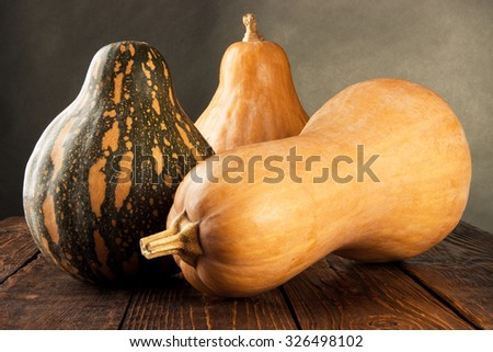 Three different pumpkin lie on a brown wooden table on a black background - stock photo