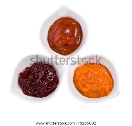 Three different sauces in a white bowl with spoons different colors on the horizontal surface isolated on white background - stock photo