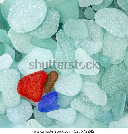 Three different sea glasses isolated on green sea glass background - stock photo