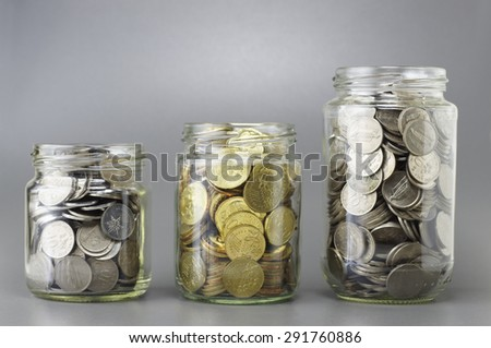 Three different size of jars full with coins - Financial Concept