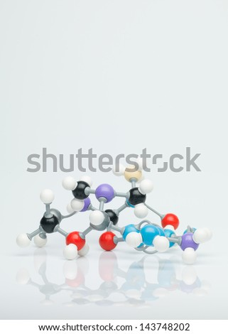 three dimensional representation molecular structure composed of multi colored spheres with grey bonds against a white background - stock photo