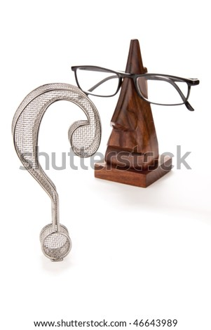 Three-dimensional wire frame question mark with a pair of reading glasses on an eyewear stand. - stock photo