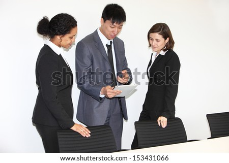 Three diverse multiethnic businesspeople having a discussion standing looking at a tablet-pc in the office - stock photo