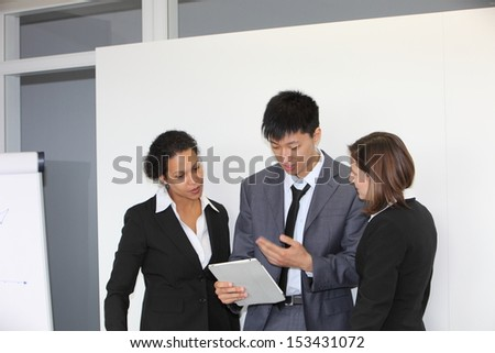 Three diverse young multiethnic business people having a team discussion standing looking at a tablet-pc in front of a presentation screen in the office