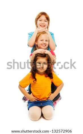 Three diversity looking kids in a row one on top of another in a vertical line, smiling, happy, smiling, isolated on white