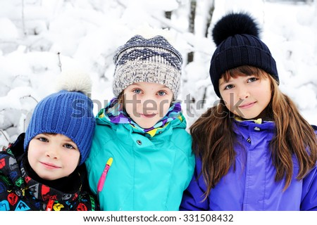 Three diversity looking kids - two girls and a boy outside on sunny winter day - stock photo