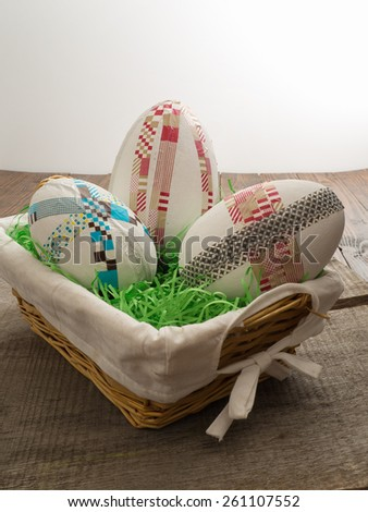 Three do-it-yourself easter eggs with colored taped on a wooden table with easter grass - stock photo