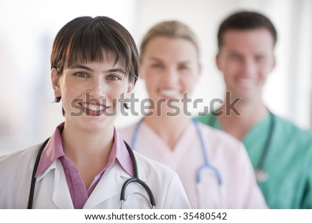 Three doctors are smiling at the camera.  Horizontally framed shot.