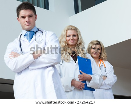 Three doctors in a hospital looking at camera - stock photo