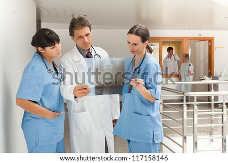 Three doctors standing in a hospital while looking at a x-ray - stock photo