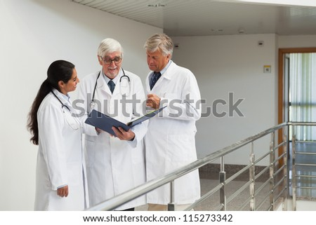 Three doctors talking in the corridor looking at patient files - stock photo