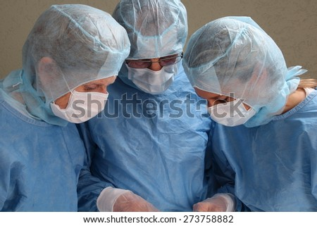 Three doctors working concentrated in a OP room - stock photo