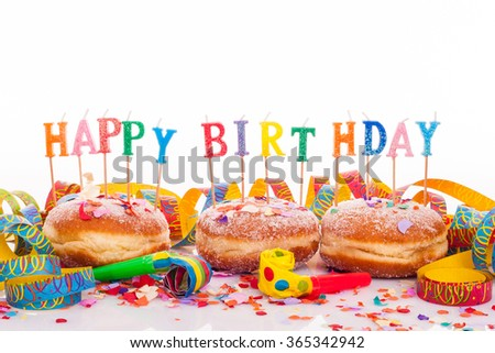 """three doughnuts with confetti and streamer - birthday decoration with candles on white background - candles with text """"happy birthday"""" - stock photo"""