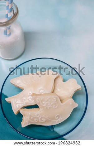 Three (dove shaped) Cookies on blue plate and milk bottle with straws - stock photo