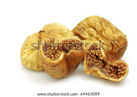 three dried and one cut fig on a white background