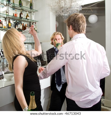 Three drunken people at the bar, guzzling the last few drops of champagne from a bottle - stock photo