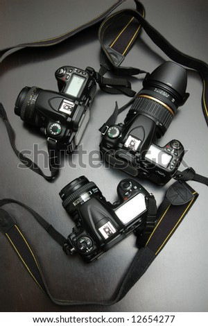 Three DSLR cameras over black background - stock photo