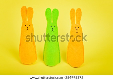 Three easter Bunnies on yellow paper background - stock photo